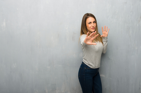 Young woman on textured wall is a little bit nervous and scared stretching hands to the front