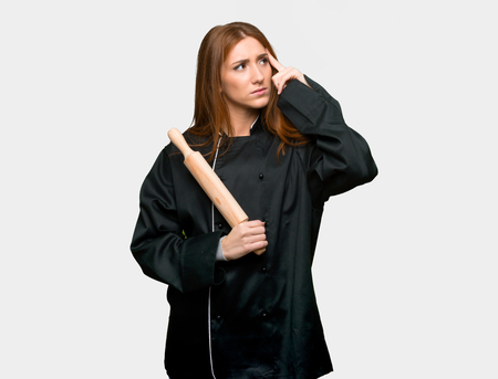 Young redhead chef woman having doubts and thinking on isolated grey background Stock Photo