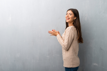 Teenager girl with sweater on a vintage wall applauding after presentation in a conference Фото со стока