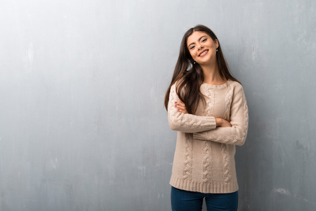Teenager girl with sweater on a vintage wall keeping the arms crossed in frontal position