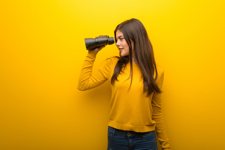 Teenager girl on vibrant yellow background and looking in the distance with binoculars