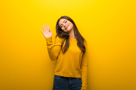 Teenager girl on vibrant yellow background saluting with hand with happy expression Standard-Bild