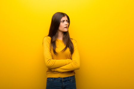 Teenager girl on vibrant yellow background with confuse face expression while bites lip