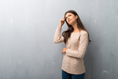 Teenager girl with sweater on a vintage wall having doubts while scratching head Stock Photo