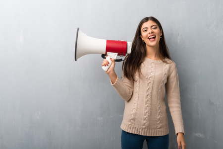 Teenager girl with sweater on a vintage wall holding a megaphone