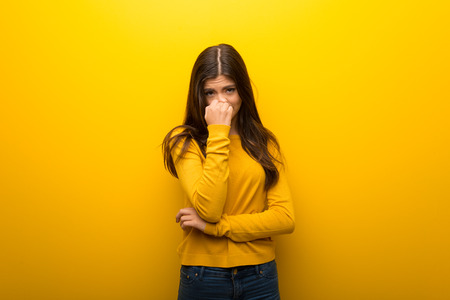 Teenager girl on vibrant yellow background having doubts Stock Photo