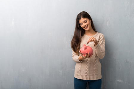 Teenager girl with sweater on a vintage wall taking a piggy bank and happy because it is full