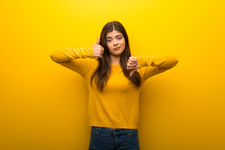 Teenager girl on vibrant yellow background making good-bad sign. Undecided between yes or not