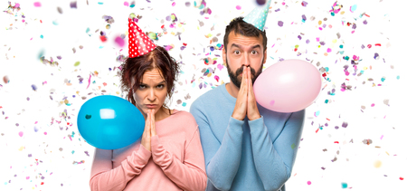 couple with balloons and birthday hats keeps palm together. Person asks for something with confetti in a party Фото со стока
