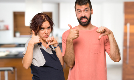 Couple avec femme enceinte faisant bon-mauvais signe. Indécis entre oui ou non à l'intérieur de la maison