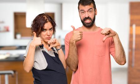 Pareja con mujer embarazada haciendo buena o mala señal. Indeciso entre sí o no dentro de casa