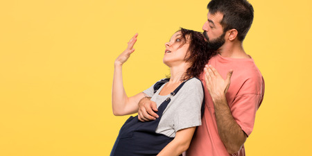 Couple with pregnant woman fainting of childbirth on isolated yellow background