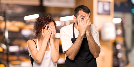 Couple of cooks covering eyes by hands and looking through the fingers Stock Photo