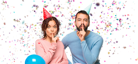 couple with balloons and birthday hats showing a sign of silence gesture putting finger in mouth with confetti in a party