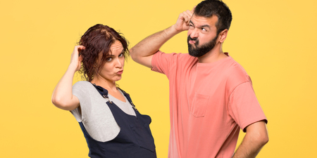 Couple with pregnant woman having doubts and with confuse face while scratching head on isolated yellow background