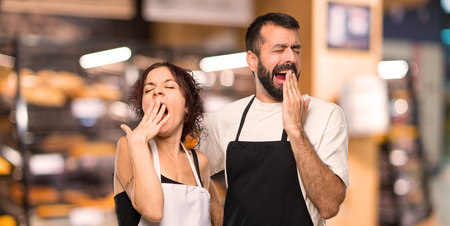 Couple of cooks yawning and covering mouth with hand. Sleepy expression Zdjęcie Seryjne