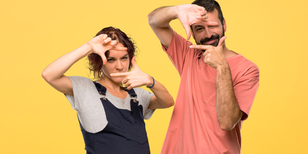 Couple with pregnant woman focusing face. Framing symbol on isolated yellow background