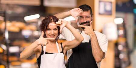Couple of cooks focusing face. Framing symbol