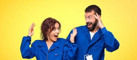 Painters with surprise and shocked facial expression on colorful background Foto de archivo
