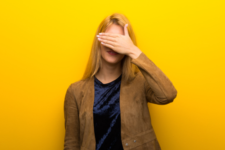 Blonde girl on vibrant yellow background covering eyes by hands. Do not want to see something
