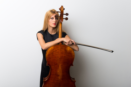 Young blonde girl with her cello posing on white wall