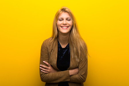 Blonde girl on vibrant yellow background keeping the arms crossed while smiling