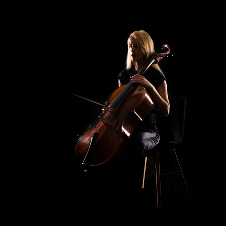 Young girl playing the cello on isolated black background Stock Photo