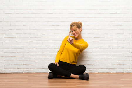 Young girl sitting on the floor showing and lifting a finger Archivio Fotografico