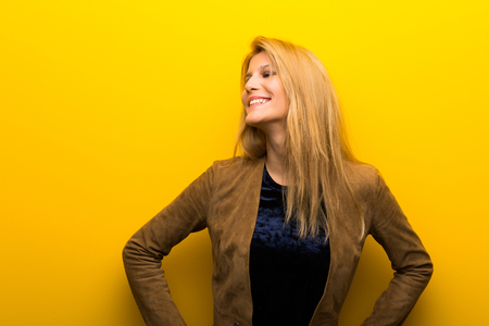 Blonde girl on vibrant yellow background posing with arms at hip and laughing