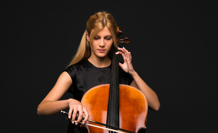 Young girl playing the cello on isolated black background 스톡 콘텐츠