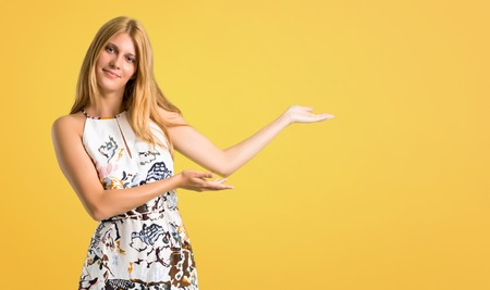 Blonde young girl in a summer dress presenting and inviting to come on yellow background