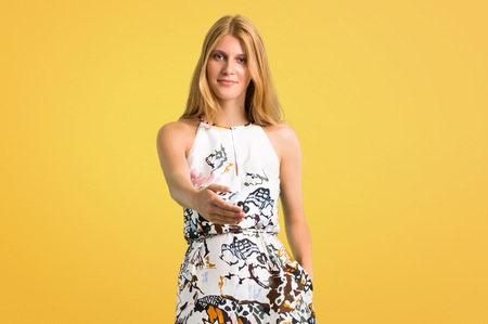 Blonde young girl in a summer dress shaking hands for closing a good deal on yellow background
