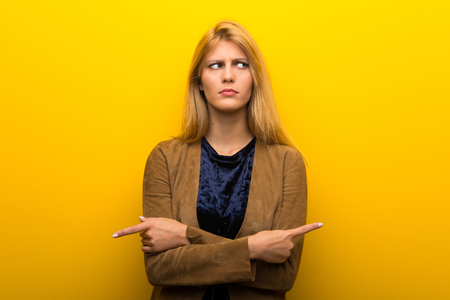 Blonde girl on vibrant yellow background pointing to the laterals having doubts Standard-Bild