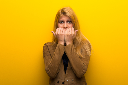 Blonde girl on vibrant yellow background is a little bit nervous and scared putting hands to mouth Foto de archivo