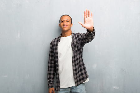 Young african american man with checkered shirt saluting with hand with happy expression