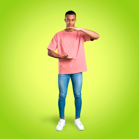 Standing young african american man holding copy space imaginary on the palm to insert an ad on colorful background