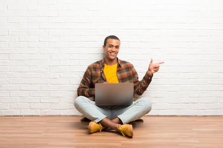 African american man sitting on the floor with his laptop pointing finger to the side in lateral position 版權商用圖片