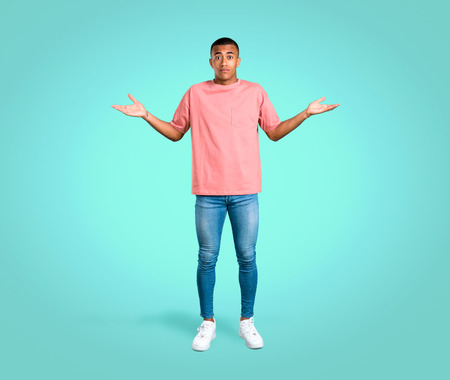 Standing young african american man having doubts and with confuse face expression while raising hands and shoulders on colorful background