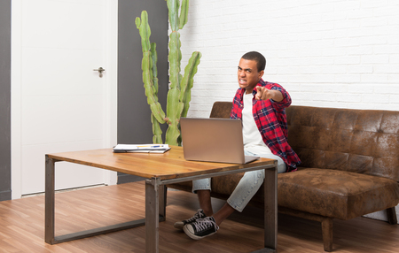 African american man with laptop in the living room frustrated by a bad situation and pointing to the front 写真素材