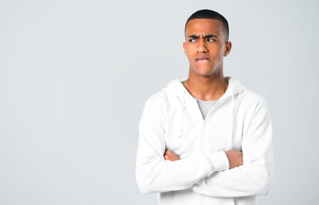 Dark-skinned young man with white sweatshirt having doubts and with confuse face expression while bites lip. Questioning an idea on grey background 版權商用圖片