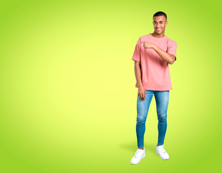 Standing young african american man pointing finger to the side and presenting a product on colorful background