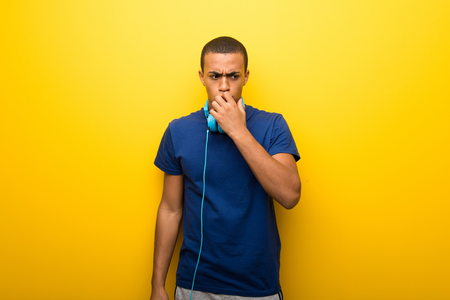 African american man with blue t-shirt on yellow background having doubts Stock Photo