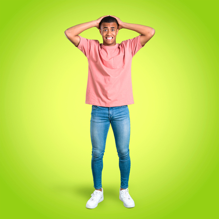 Standing young african american man annoyed angry in furious gesture. Negative expression on colorful background