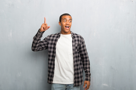 Young african american man with checkered shirt intending to realizes the solution while lifting a finger up