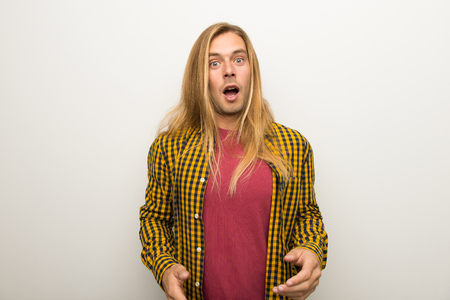 Blond man with long hair and with checkered shirt with surprise and shocked facial expression