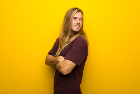 Blond man with long hair over yellow wall looking over the shoulder with a smile
