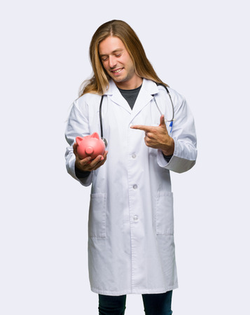 Doctor man holding a piggybank on isolated background