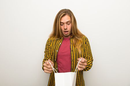 Blond man with long hair and with checkered shirt surprised while holding a lot of shopping bags