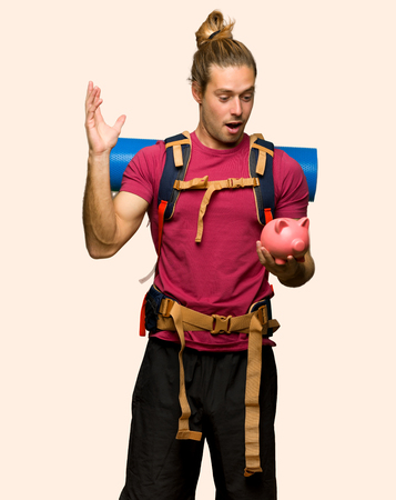 Hiker man with mountain backpacker surprised while holding a piggybank on isolated background