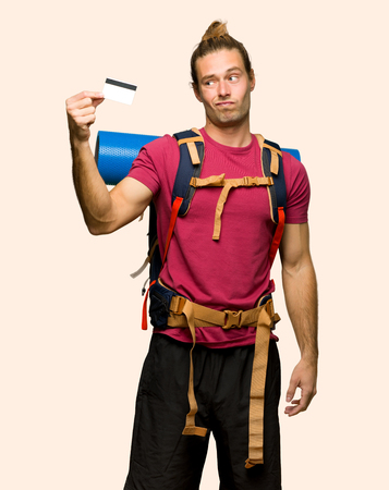 Hiker man with mountain backpacker taking a credit card without money on isolated background Archivio Fotografico